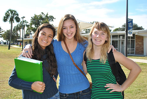 Three Female student  on the grassy area outside Natural Sciences.